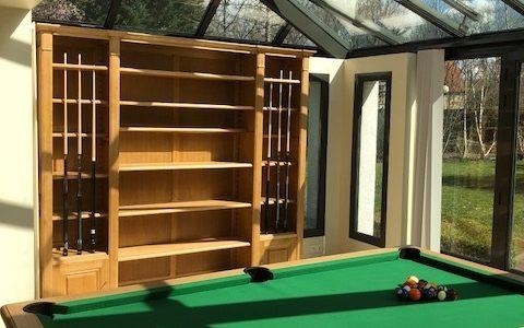 Conception d'une bibliothèque en bois naturel formant porte queues de billard