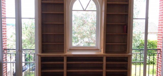 Bibliothèque sur mesure en châtaignier venant encadrer trois fenêtres
